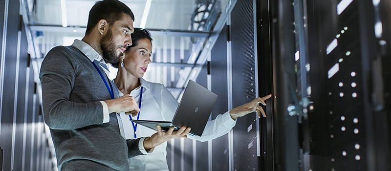 Two people in a server room.
